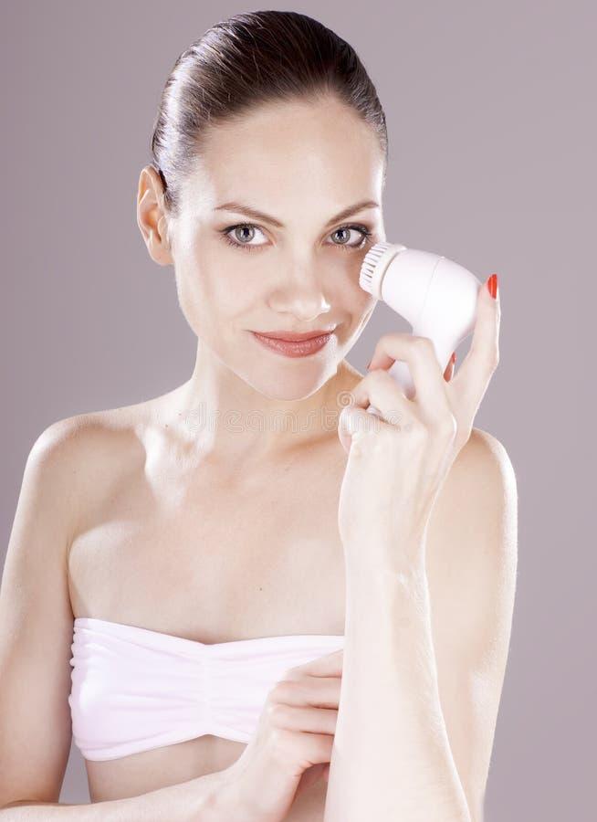 Femme avec la brosse pour le massage facial profondément de nettoyage photo stock
