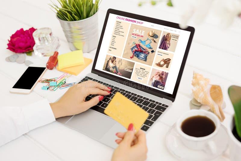 Femme avec la carte de crédit achetant de nouveaux vêtements en ligne image libre de droits