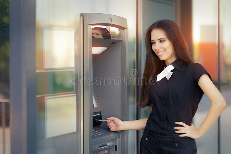 Femme avec la carte de crédit au distributeur automatique de billets d'atmosphère photo stock