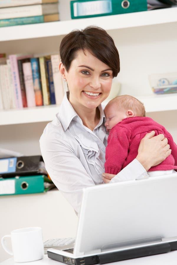 Femme avec la chéri nouveau-née travaillant de la maison photo stock