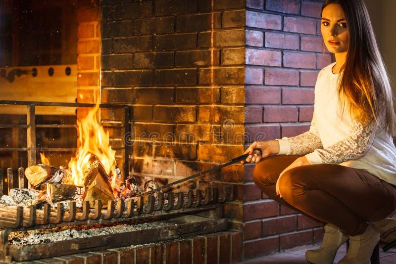 Femme avec la cheminée de tisonnier de fer de feu à la maison image libre de droits