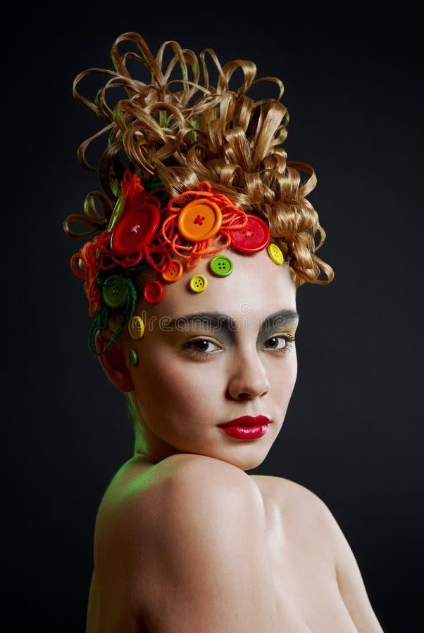 Femme avec la coiffure de créativité avec le bouton coloré image stock