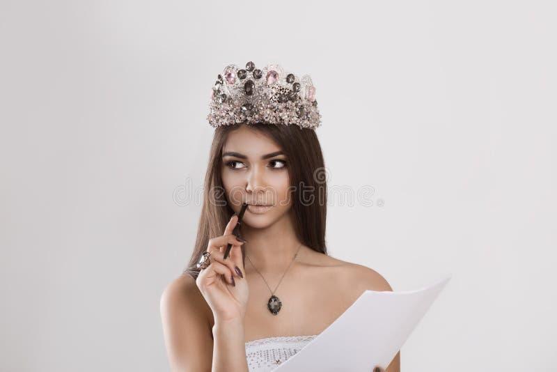 Femme avec la couronne en cristal recherchant l'analyse de pensée tenant des documents sur papier photographie stock libre de droits