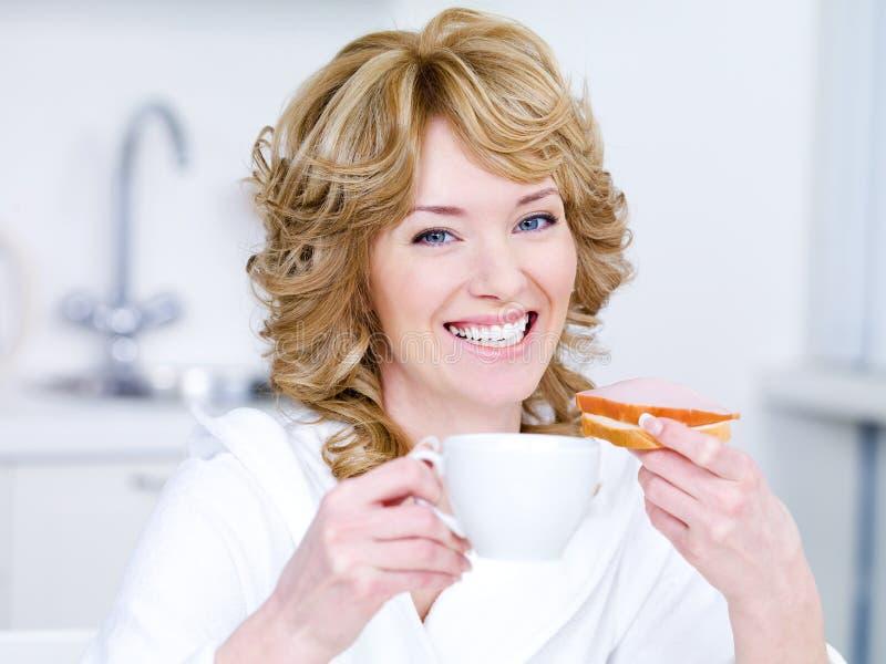 Femme avec la cuvette de café prenant le petit déjeuner photo stock