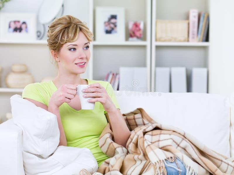 Femme avec la cuvette de la boisson de réchauffement