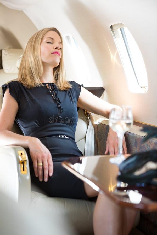Femme avec la détente fermée par yeux dans le jet privé images stock