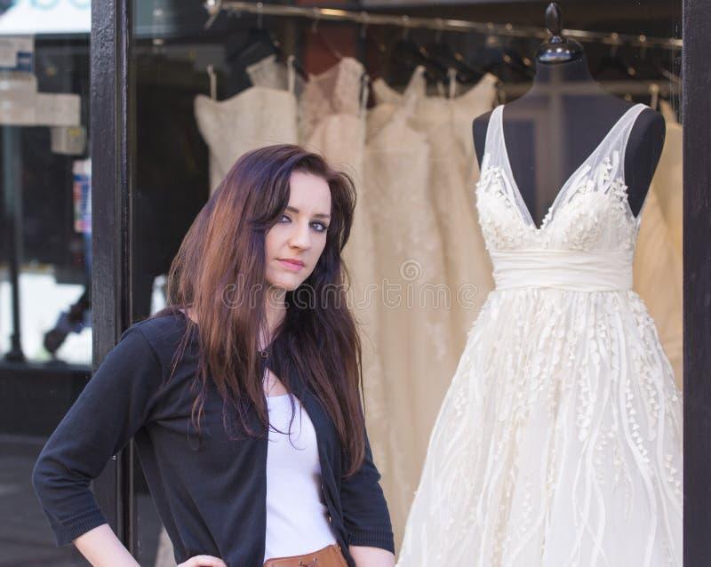 Femme avec la fenêtre de boutiques de robes de mariage photo stock