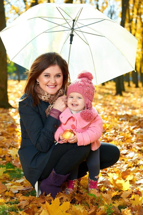 Femme avec la fille d'enfant sous le parapluie en parc de ville d'automne, famille heureuse photo libre de droits