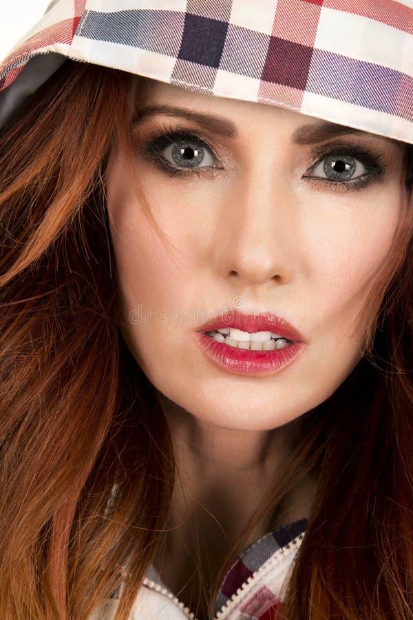 Femme avec la fin rouge de capot de plaid de cheveux sérieuse photo libre de droits