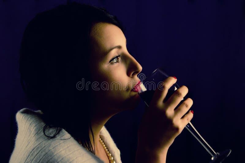 Femme avec la glace de vin rouge images stock