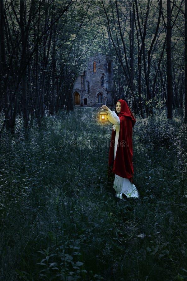 Femme avec la lanterne dans la forêt et le château photographie stock libre de droits