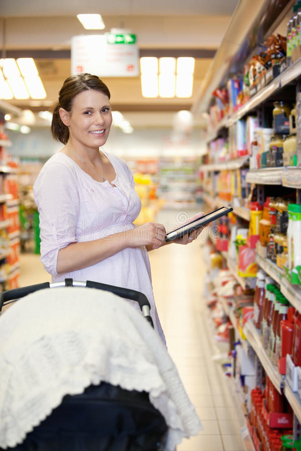 Femme avec la liste d'achats sur l'ordinateur de tablette photographie stock libre de droits
