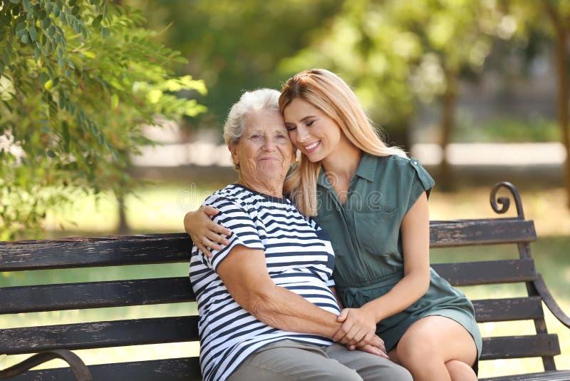 Femme avec la mère pluse âgé sur le banc image stock