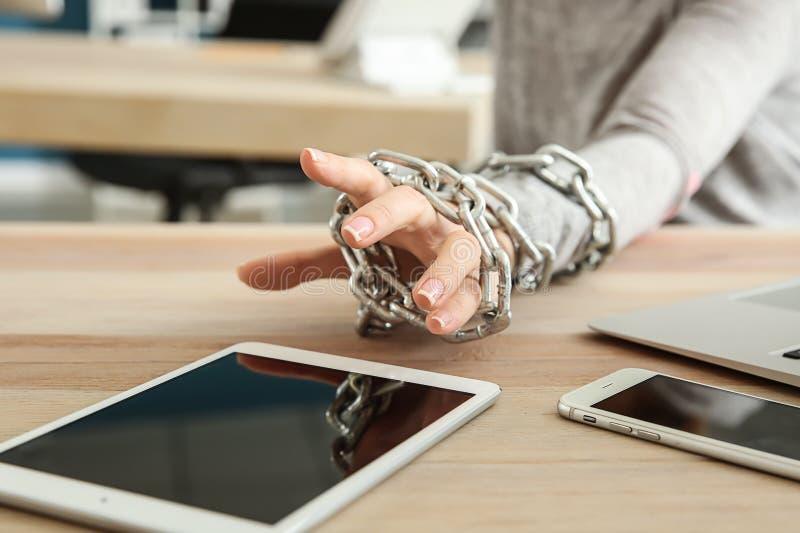 Femme avec la main enchaînée atteignant pour la tablette à la table en bois Concept de d?pendance photographie stock libre de droits