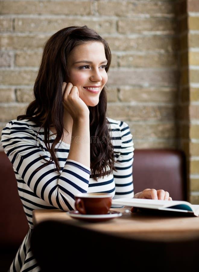 Femme avec la main sur Chin Looking Away In Cafeteria photographie stock libre de droits
