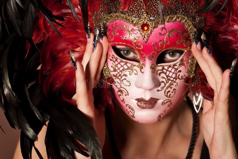 Femme avec la manucure sur le masque vénitien de prise de doigt photo stock