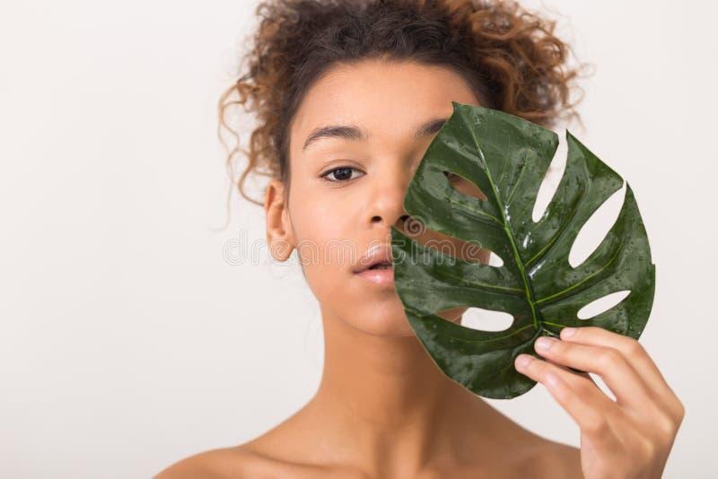 Femme avec la moitié tropicale de bâche de feuille du visage photos libres de droits