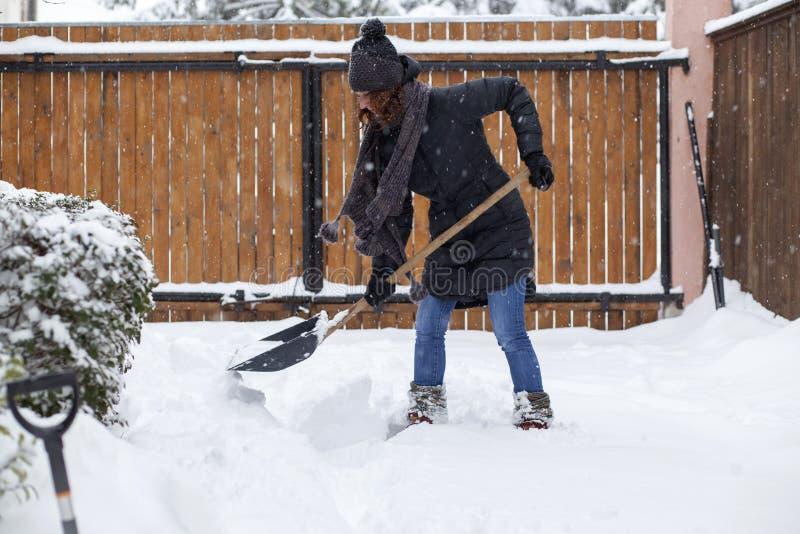 femme avec la neige de nettoyage de pelle D?blayement d'hiver Enlever la neige après tempête de neige photos stock
