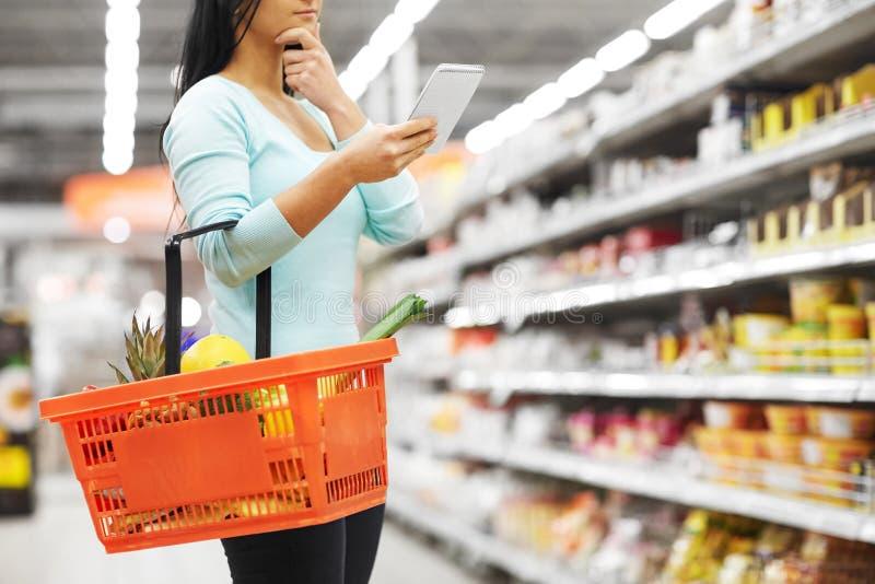 Femme avec la nourriture dans le panier à provisions au supermarché images stock