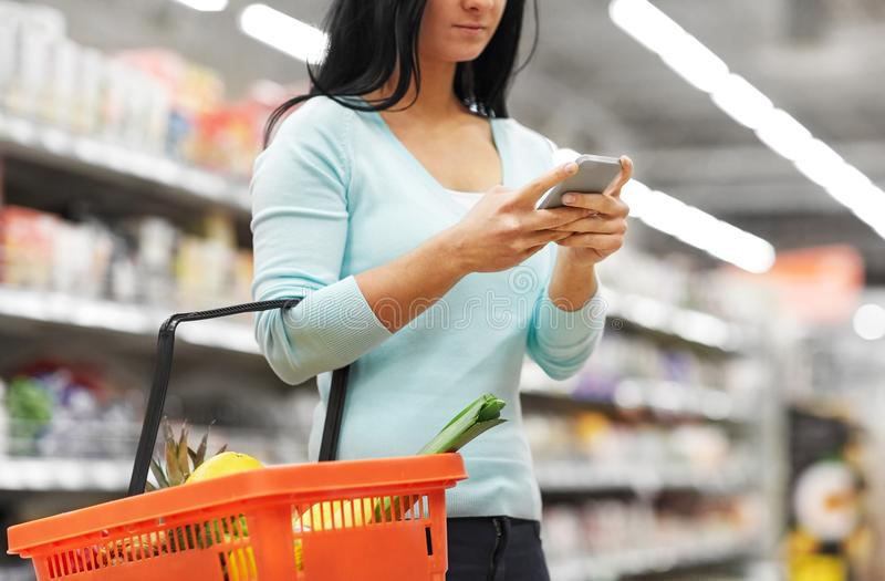 Femme avec la nourriture de achat de smartphone au supermarché photos stock