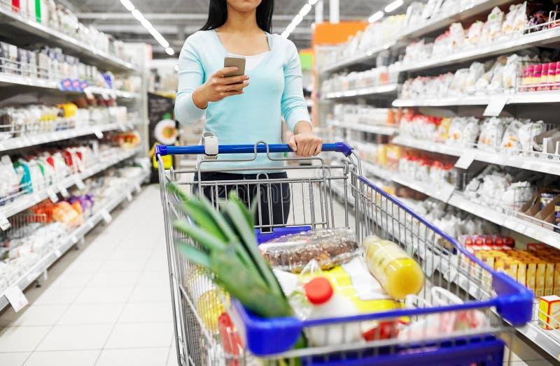 Femme avec la nourriture de achat de smartphone au supermarché photo libre de droits