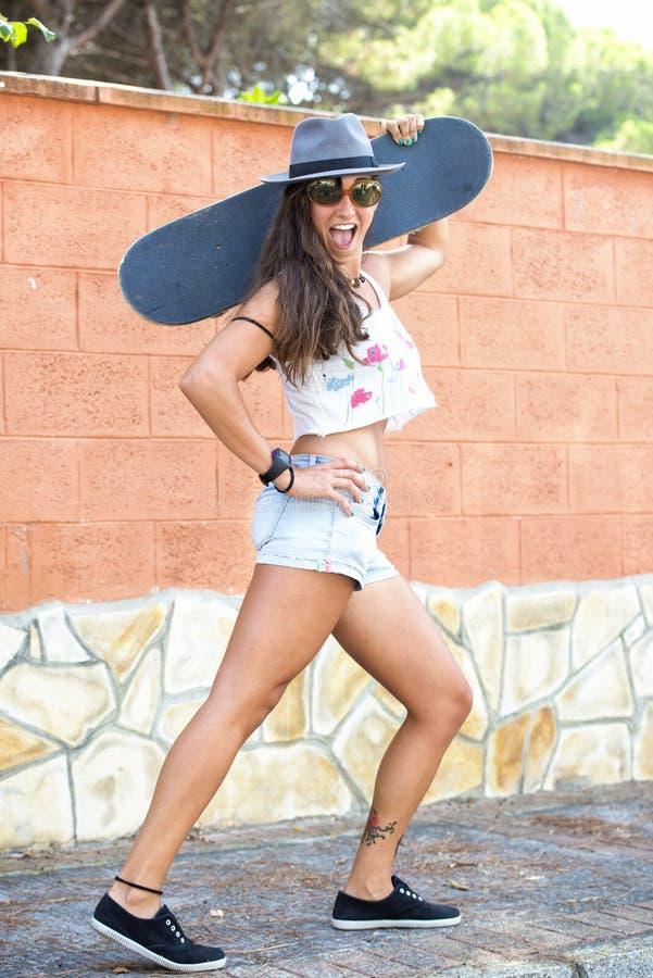 Femme avec la planche à roulettes sur la rue photographie stock