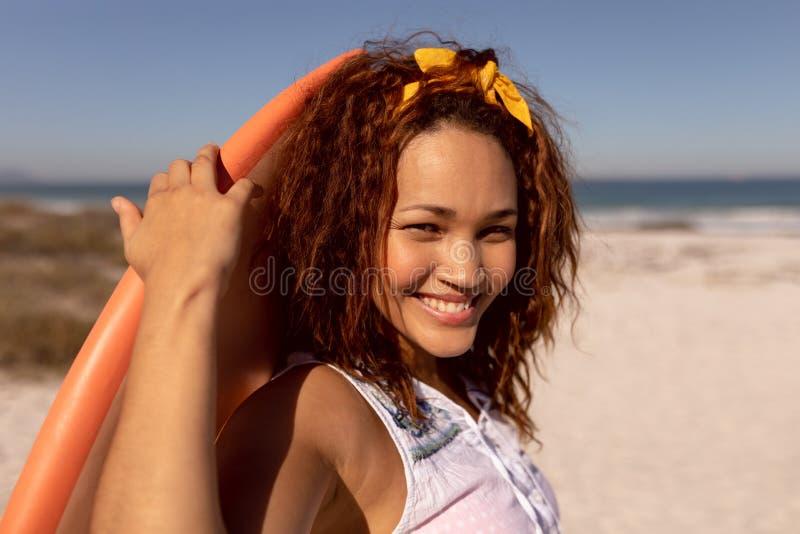 Femme avec la planche de surf regardant la caméra sur la plage au soleil photo libre de droits