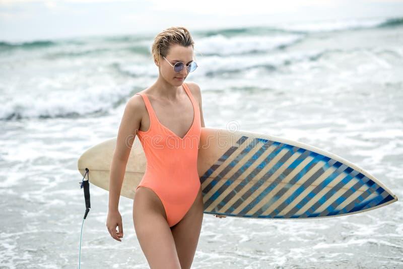 Femme avec la planche de surf sur la plage photos libres de droits