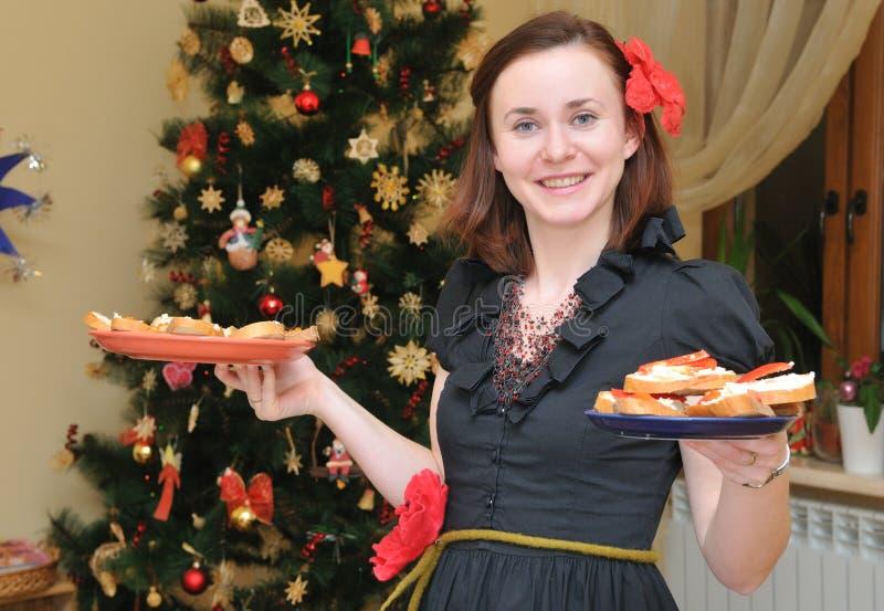 Femme avec la plaque près du Noël-arbre image stock