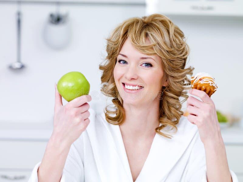Femme avec la pomme et gâteau dans la cuisine photos libres de droits