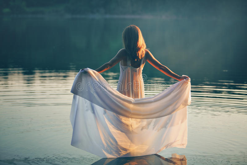 Femme avec la robe blanche dans un lac au coucher du soleil image libre de droits