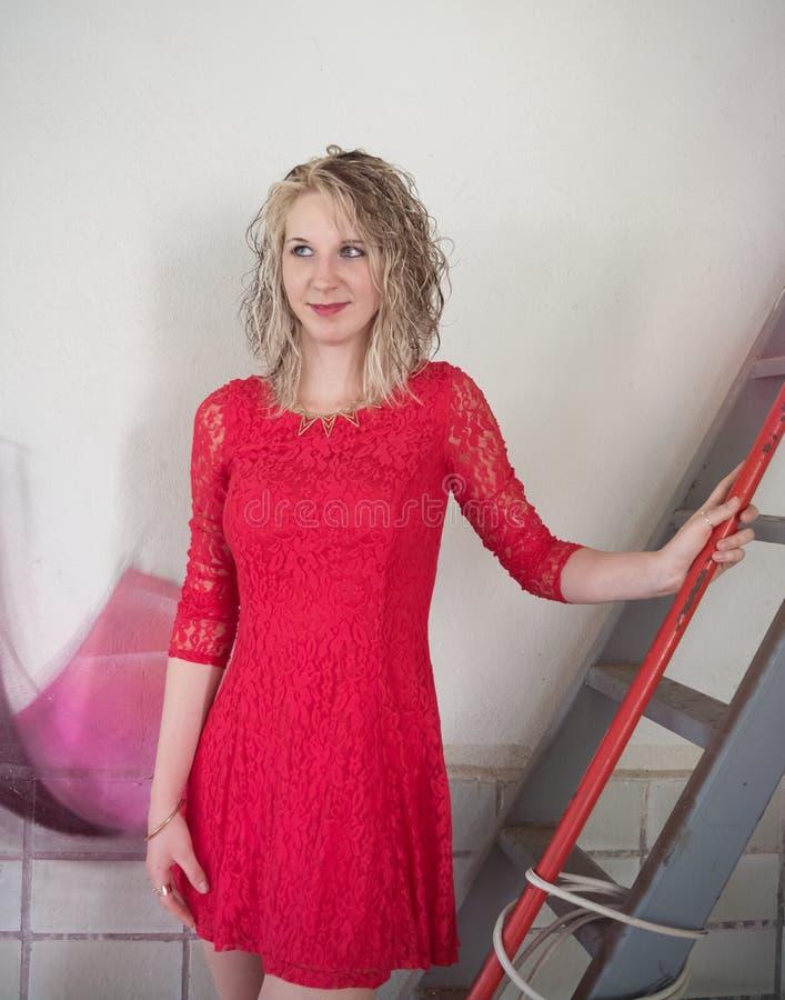 Femme avec la robe rouge sur l'échelle II photo stock