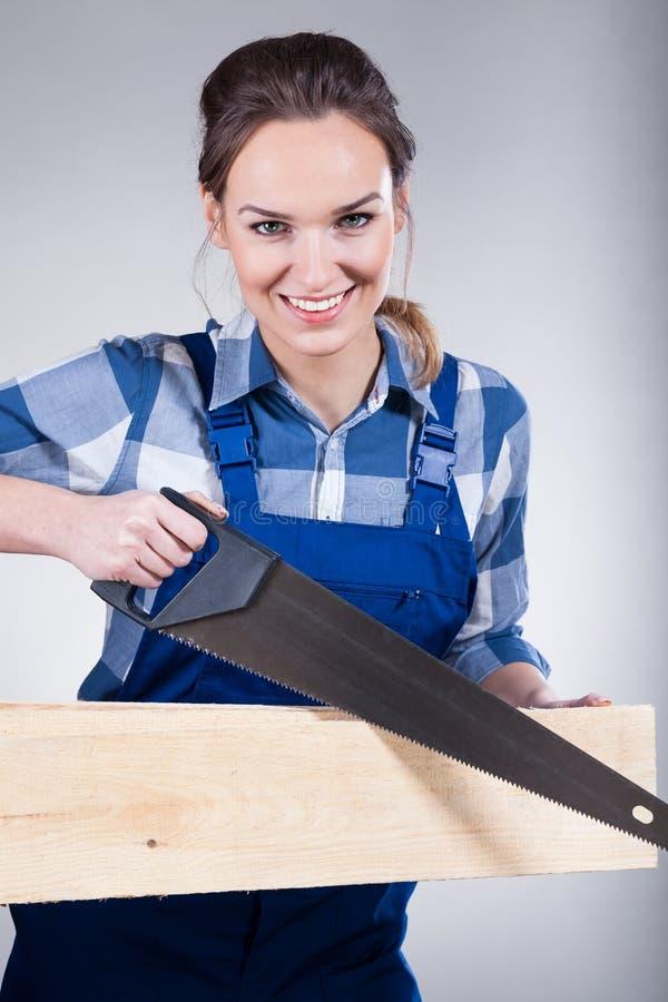 Femme avec la scie à main images stock
