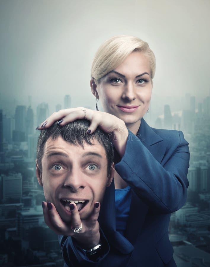 Femme avec la tête de l'homme dans sa main image libre de droits