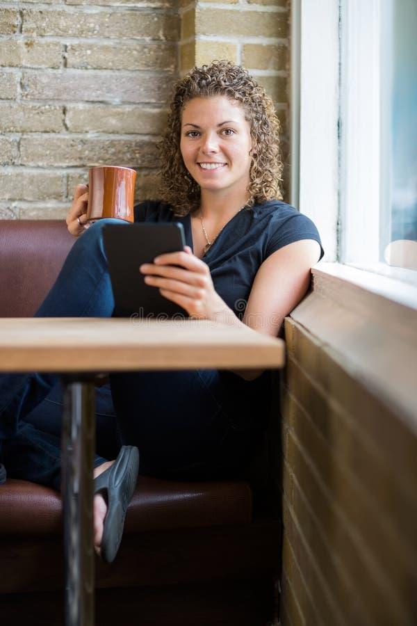Femme avec la Tablette de Digital et la tasse de café dedans photo stock