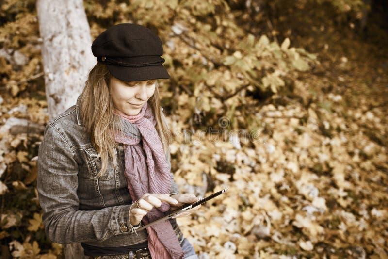 Femme avec la tablette de Digitals dans la forêt d'automne images libres de droits