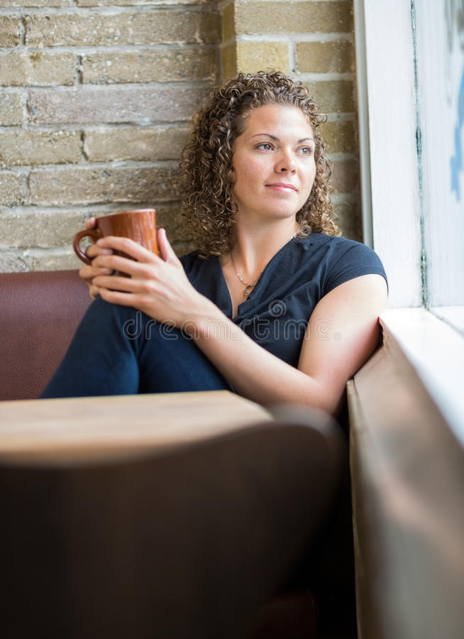 Femme avec la tasse de café dans le cafétéria photographie stock libre de droits