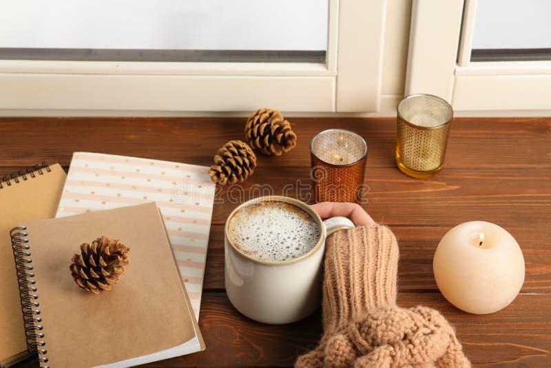 Femme avec la tasse de caf? et de carnets ? la fen?tre ? l'int?rieur, plan rapproch image libre de droits