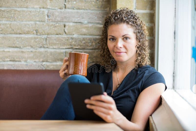 Femme avec la tasse de café et la Tablette de Digital en café photo libre de droits