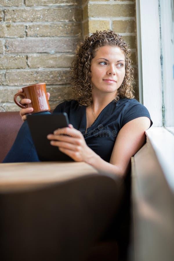 Femme avec la tasse de café et la Tablette de Digital en café photographie stock libre de droits