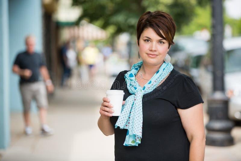 Femme avec la tasse de café jetable sur le trottoir photo libre de droits