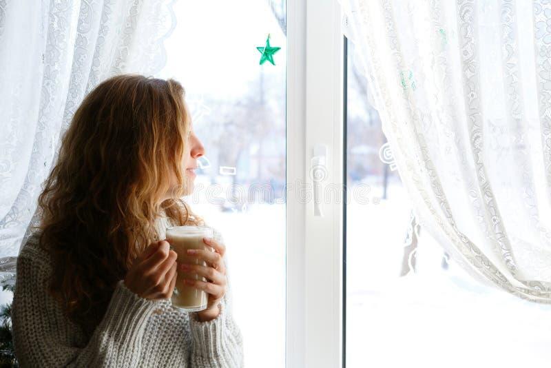 Femme avec la tasse de thé dans des ses mains regardant par la fenêtre image libre de droits