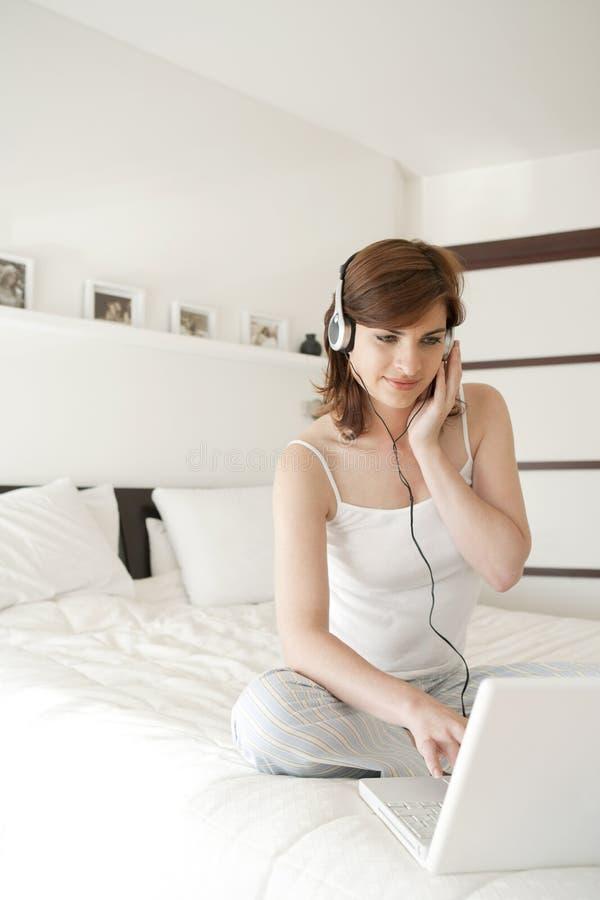 Femme avec la technologie dans la chambre à coucher photo libre de droits
