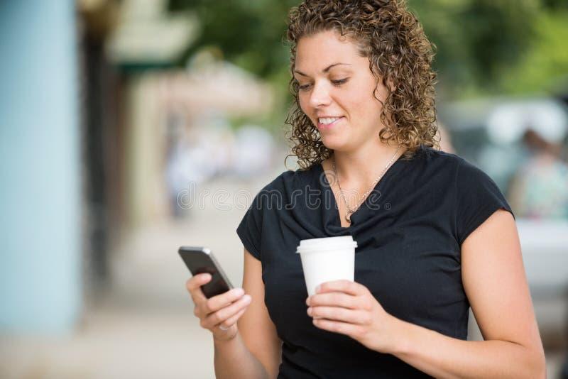 Femme avec la transmission de messages de tasse de café par Smartphone images libres de droits