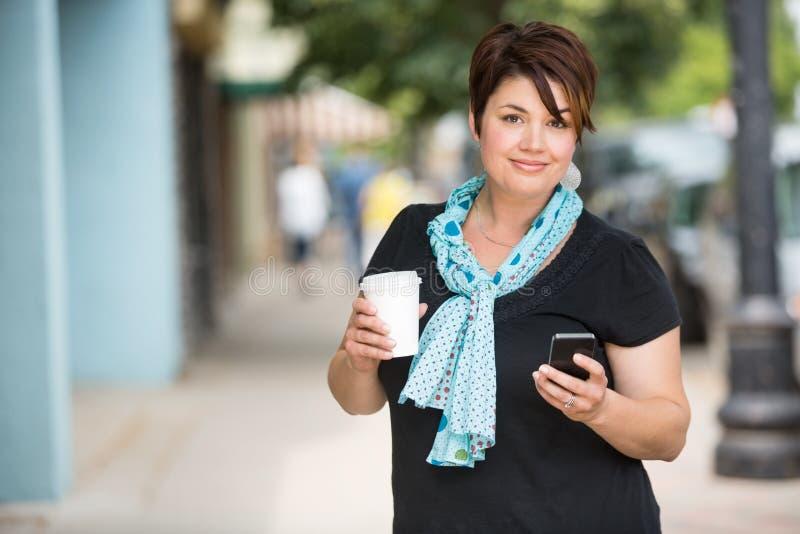 Femme avec la transmission de messages de tasse de café sur Smartphone image libre de droits