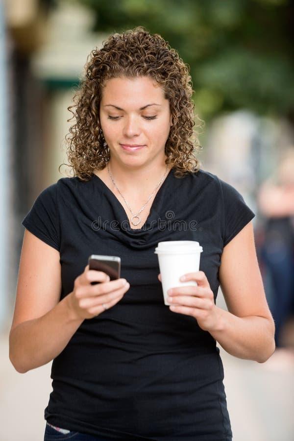 Femme avec la transmission de messages de tasse de café sur Smartphone photos libres de droits