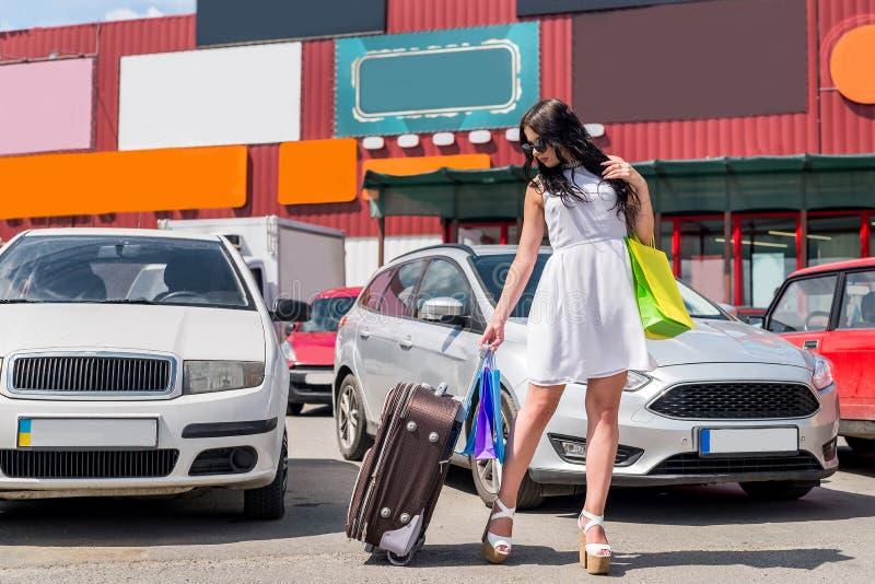 femme avec la valise et sacs à provisions près de voiture image stock