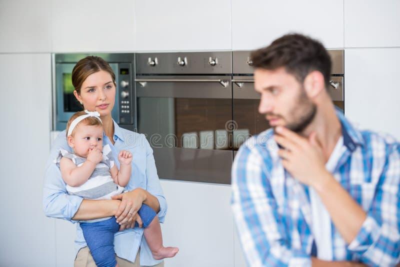 Femme avec le bébé regardant le mari tendu photographie stock