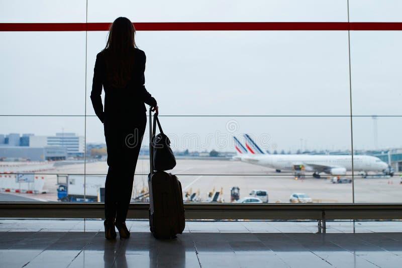 Femme avec le bagage de main dans l'aéroport international, regardant par la fenêtre des avions photographie stock