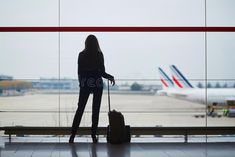 Femme avec le bagage de main dans l'aéroport international, regardant par la fenêtre des avions images stock
